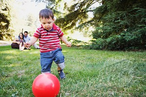 Toddler boy kicking red ball